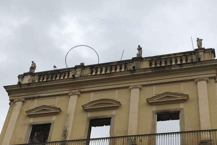 Uma das estátuas de deusas que ficam no topo do Museu Nacional caiu nesta madrugada (imagem em destaque)