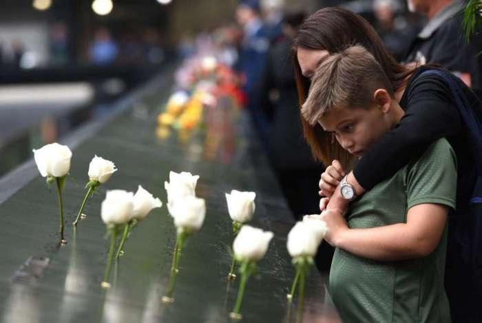 Um menino e sua mãe prestam homenagens na cerimônia anual no marco zero do World Trade Center