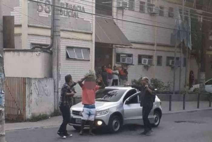 Acusado do roubo sendo rendido em frente à delegacia