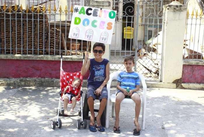 Enzo (centro), 8 anos, espera a distribuição de doces sentado na calçada com aviso no cartaz colorido