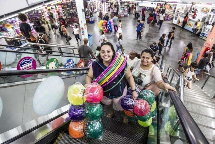 Dandara Couto (de preto), de 29 anos, compra brinquedos no Mercadão de Madureira para doar. Ela repete a tradição há cinco anos