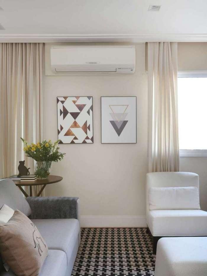 Na sala com sofá, cortinas e poltronas neutras, o morador pode investir em um tapete escuro