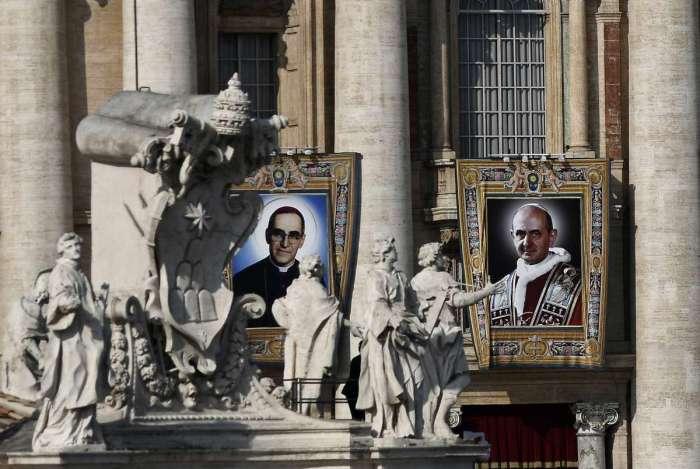Retratos do Papa Paulo VI (à direita) e do martirizado salvadorenho Oscar Romero (à esquerda) são vistos durante a missa de canonização na Praça de São Pedro, no Vaticano