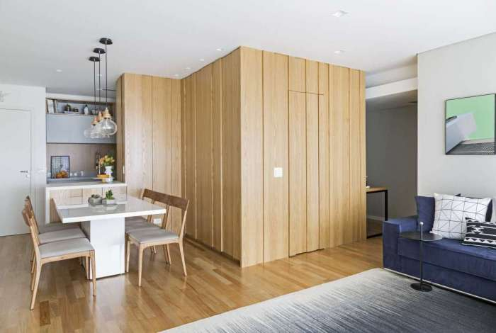 Painel de madeira camufla entrada do lavabo e ainda guarda um espaço para armário de louças de cozinha
