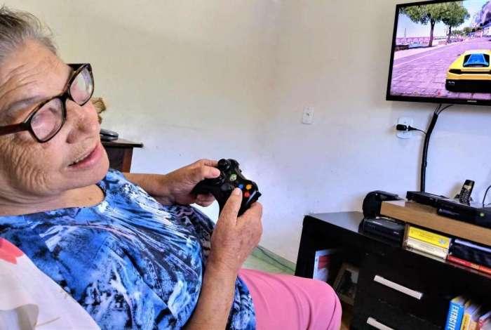 A aposentada Maria Dóra Godinho Alves começou a jogar videogame aos 76 anos, incentivada pelo filho, Rafael Alves, 46. Ajuda no tratamento de demência e Alzheimer. Arquivo Pessoal