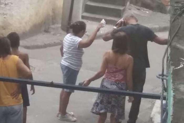 A foto mostra o morador limpando o sangue depois de ser atingido por estilhaços de bala