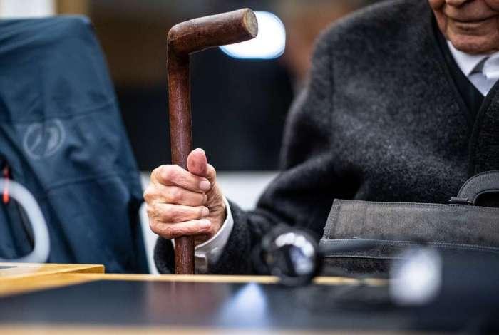 Ex-guarda de 94 anos segura sua bengala enquanto aguarda no tribunal a continuação de seu julgamento na corte regional de Muenster, no oeste da Alemanha