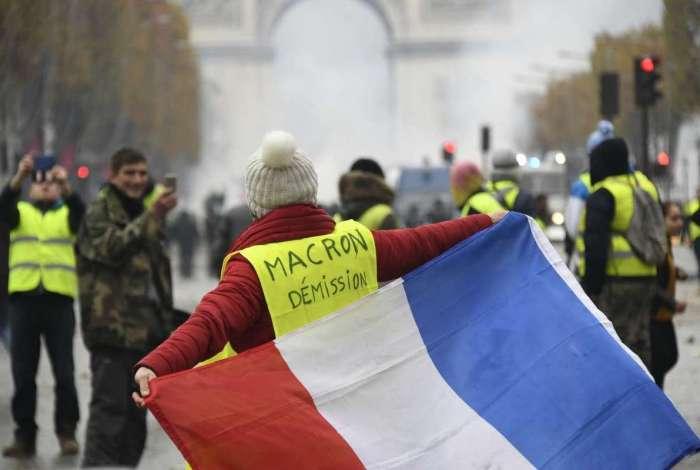 Mulher usa colete amarelo com a inscrição 'Renuncia Macron' nos Champs-Elysées, em Paris (Bertrand Guay /AFP)