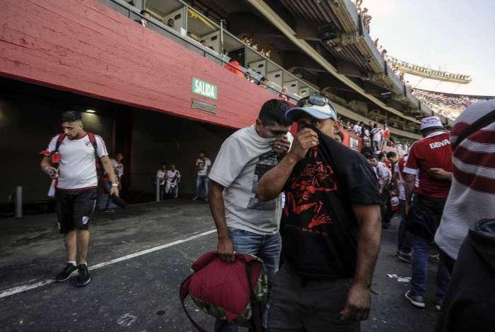 Torcedores do River Plate cobrem o rosto por causa do gás de pimenta jogado pela polícia
