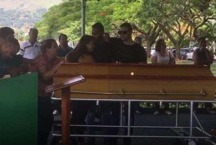 Maisa Carvalhosa (de blusa listrada) chora sobre o caixão da filha