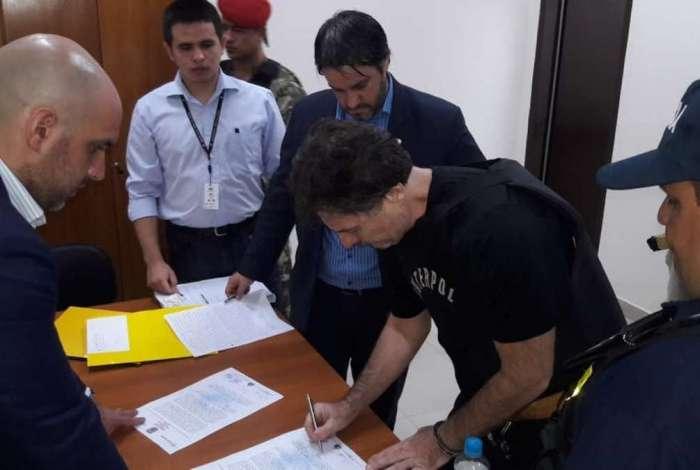 Bruno Farina assina documento antes de ser enviado de volta ao Brasil