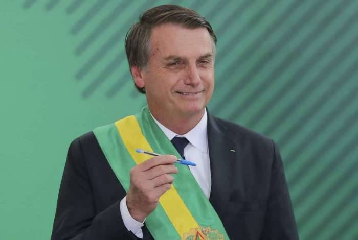 Brazil's new President Jair Bolsonaro poses with the pen used during the swearing-in ceremony for the minsters at the Planalto Palace in Brasilia on January 1, 2019, after his own inauguration at the national Congress. - Bolsonaro takes office with promises to radically change the path taken by Latin America's biggest country by trashing decades of centre-left policies. (Photo by Sergio LIMA / AFP)