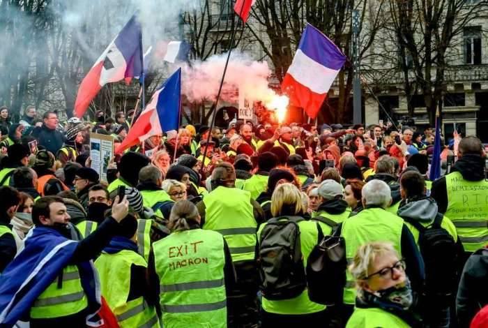 Manifestantes de coletes amarelos protestando e queimando bandeira da França em Paris