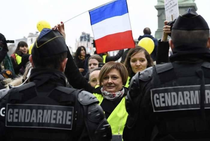 Mulheres com bandeiras francesas se postam à frente de policiais durante manifestação dos 'coletes amarelos' ontem, em Paris