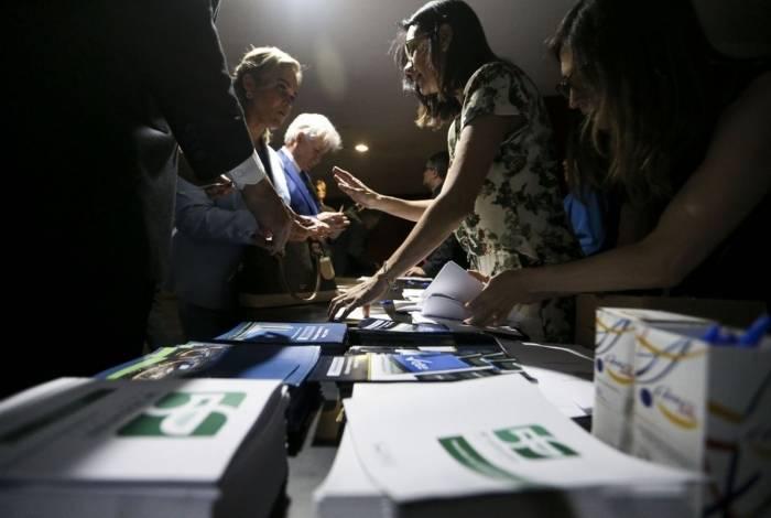 Deputados recebem broches oficiais de identificação durante os preparativos para a posse dos parlamentares