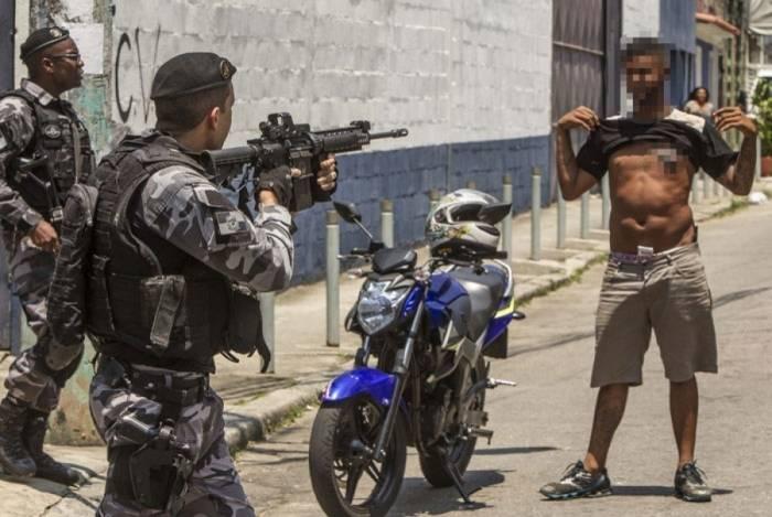 Um morador é abordado por policiais militares durante operação