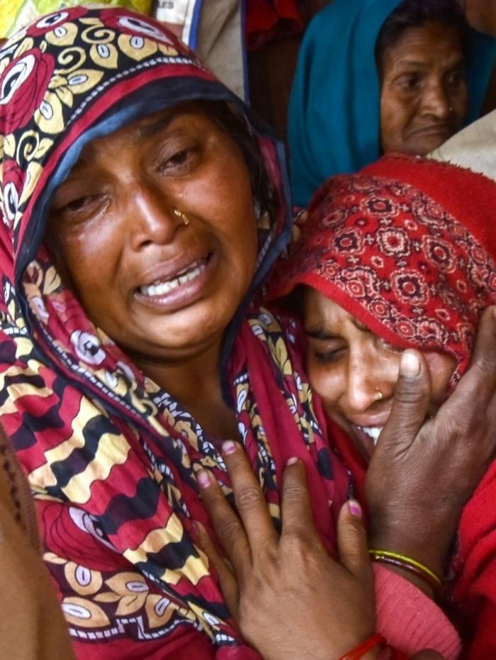 Parentes de vítimas que morreram após consumo de álcool tóxico choram no Hospital Civil de Saharanpur, em Saharanpur, no estado de Uttar Pradesh, no norte da Índia