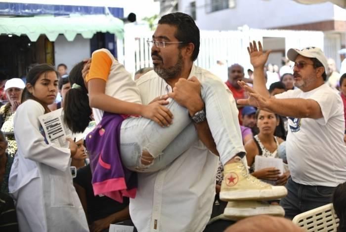 Um voluntário do movimento 'Coalizão Ajuda e Liberdade' carrega uma menina desmaiada durante um campo de atenção médica em Caracas