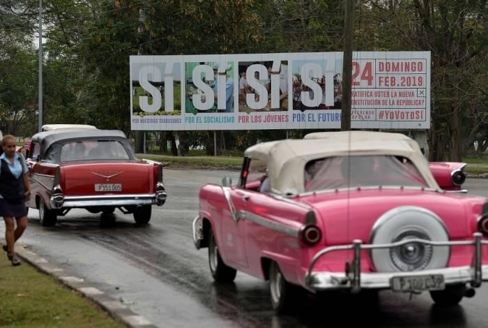 Velhos carros americanos dirigem perto de um cartaz de campanha do governo incentivando a votar a Constituição em Havana