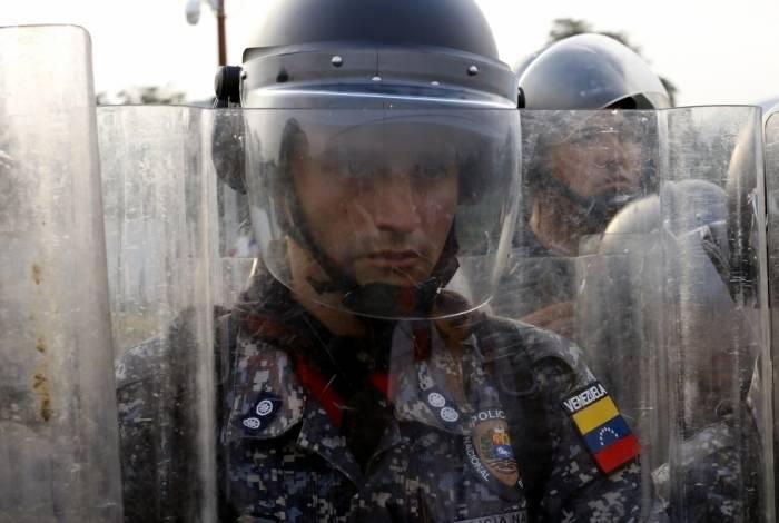Um policial venezuelano mantém guarda em cordão enquanto cidadãos pedem que eles deixem ajuda humanitária passar na Ponte Simon Bolivar, em Cucuta, na Colombia