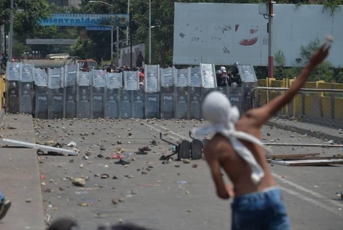 Manifestante enfrenta policiais venezuelanos na ponte Simón Bolívar, em Cucuta (Colômbia). Ontem, houve confronto na fronteira com o Brasil