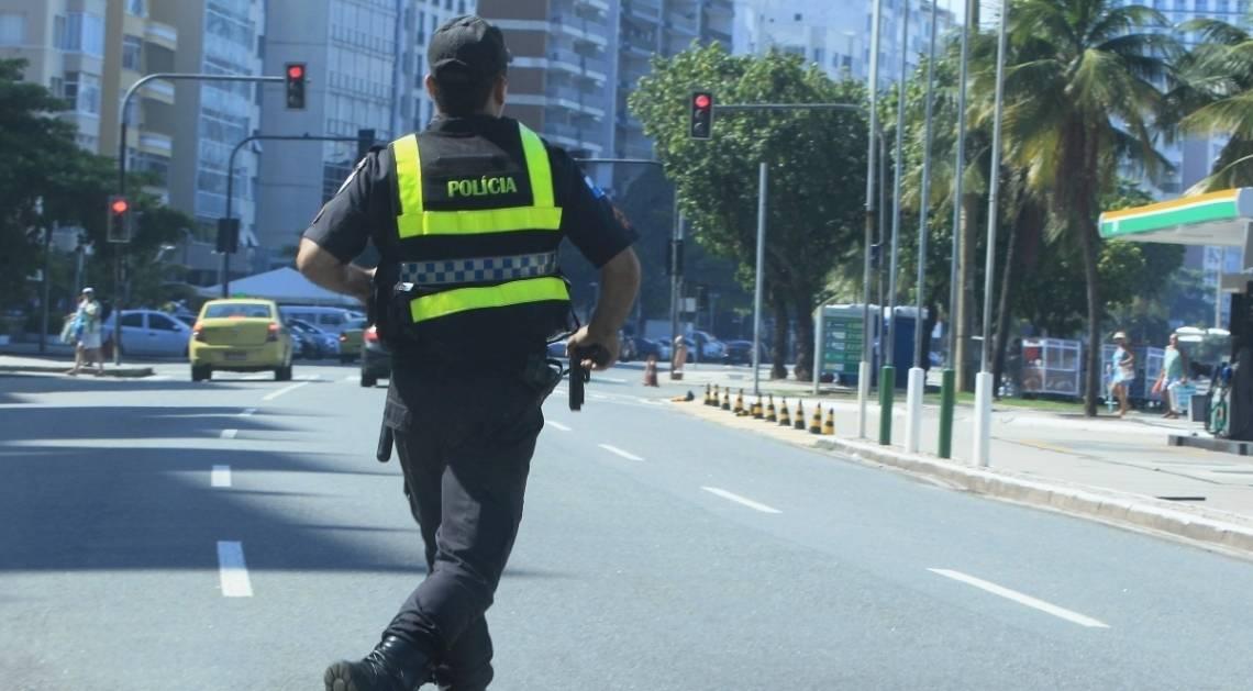 Policial corre com arma na mão no Calçadão do Posto 6, em Copacabana, para tentar prender assaltante