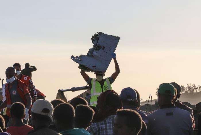 Homem carrega pedaço de destroços no local do acidente de um voo da Ethiopian Airlines em Nairóbi perto de Bishoftu, Etiópia