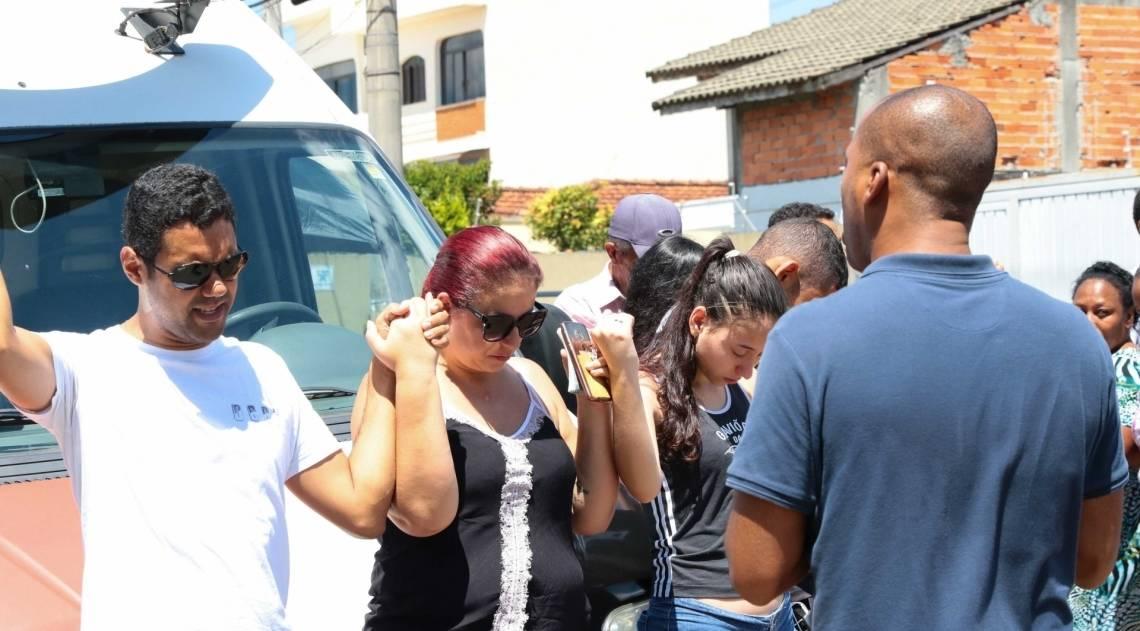 Grupo faz oração em frente à Escola Estadual Raul Brasil, em Suzano, Grande São Paulo, onde ataque deixou 10 mortos e nove feridos, entre alunos, funcionários do colégio e os atiradores, que se suicidaram
