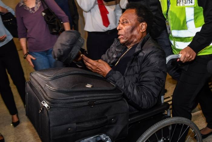 Pelé, de cadeira de rodas, no desembarque: agradecimento por orações