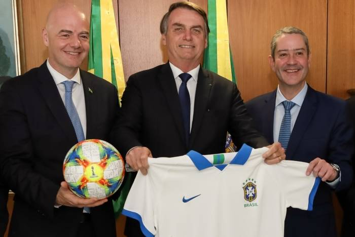 Handout picture released by Brazilian Presidency showing Brazilian President Jair Bolsonaro (C) holding a Brazilian National Team jersey gifted by FIFA President Gianni Infantino (L) and Brazilian Football Confederation (CBF) President Rogerio Caboclo during a meeting at Planalto Palace in Brasilia, on April 10, 2019. - Brazil will host the 2019 Copa America football tournament between June 14 and July 7. (Photo by MARCOS CORREA / BRAZILIAN PRESIDENCY / AFP) / RESTRICTED TO EDITORIAL USE - MANDATORY CREDIT
