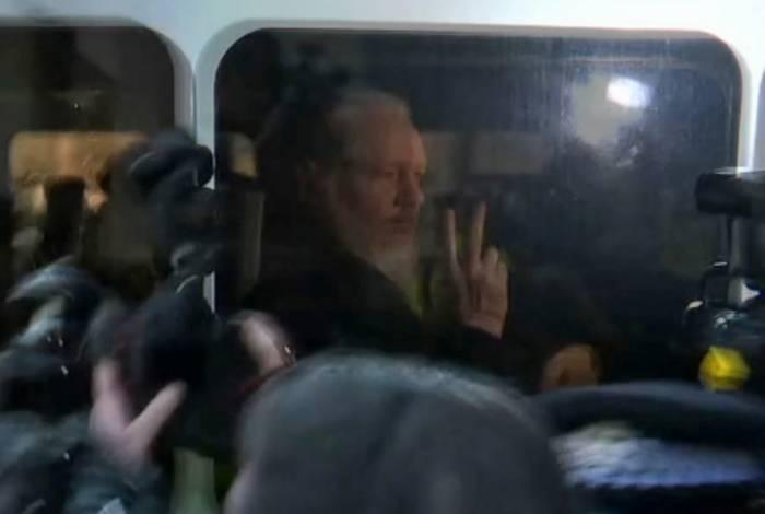 O australiano Julian Assange faz sinal para  fotógrafos e cinegrafistas