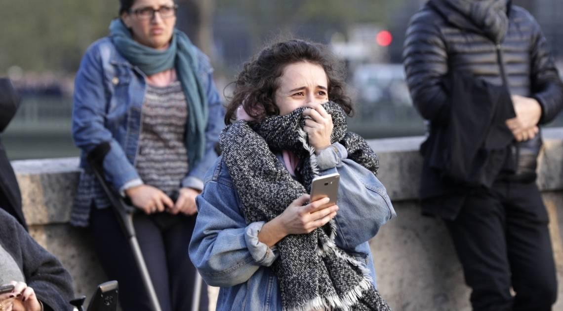 Pessoas observam a catedral de Notre-Dame em chamas, em Paris