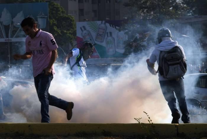 Venezuelanos correm de bomba de efeito moral durante confronto com Forças de Segurança de Caracas