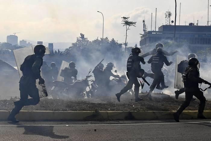 Membros da Guarda Nacional Bolivariana, leais ao presidente venezuelano Nicolas Maduro, correm sob uma nuvem de gás lacrimogêneo