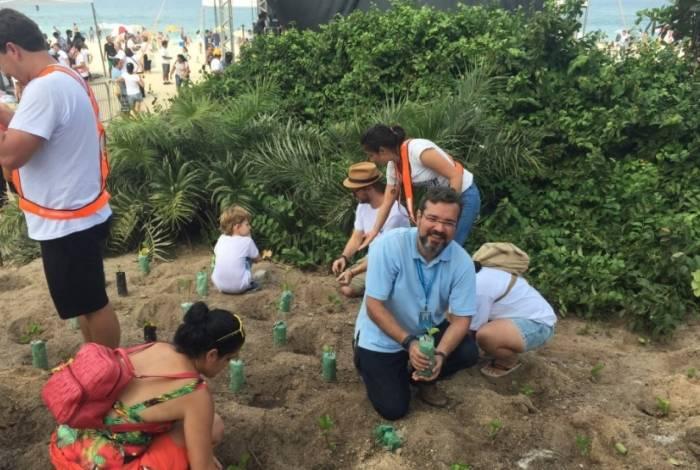Pessoas presentes no evento realizam o replantio da vegetação