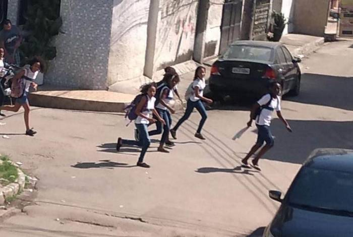 Crianças, na saída de escola na Vila do João, na Maré, correm durante tiroteio: este ano já houve 1.410 casos