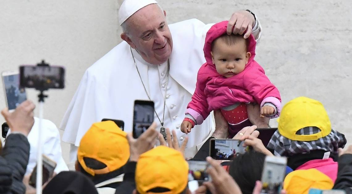 Papa Francisco com bebê quando ele chega para sua audiência geral semanal na Praça de São Pedro, no Vaticano, em 15 de maio de 2019