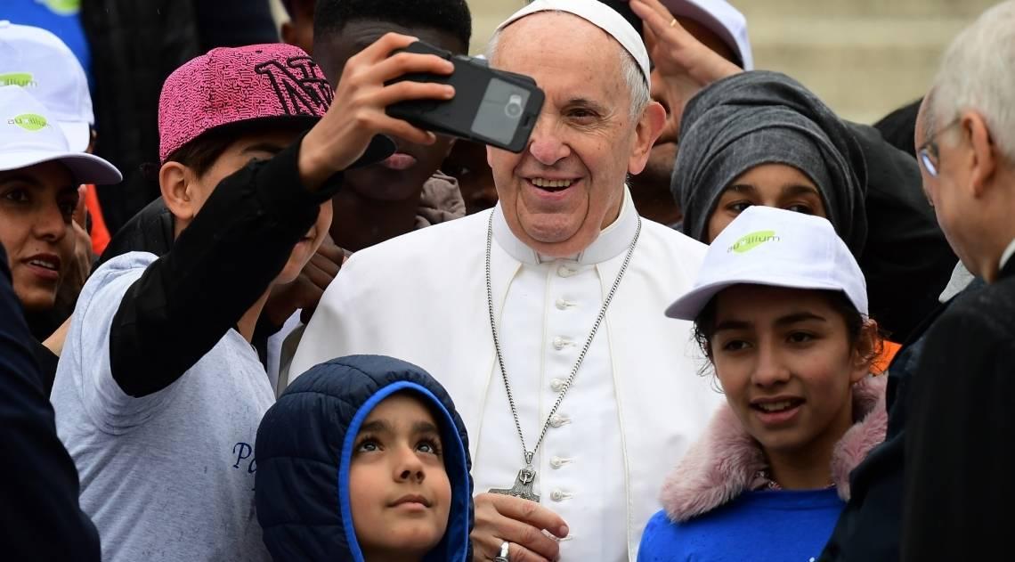 Papa Francisco posa para uma selfie com alguns refugiados na Praça de São Pedro no final de sua audiência geral semanal em 15 de maio de 2019 no Vaticano