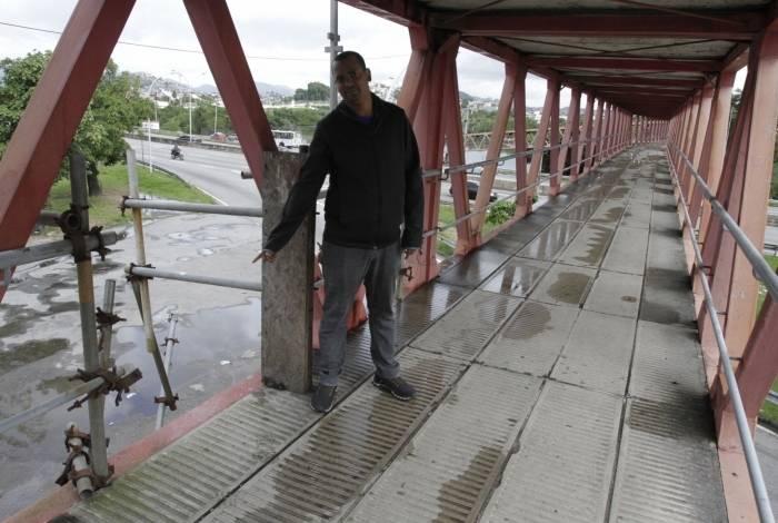 O vigilante Cléber Luiz mostra buraco na grade de proteção na passarela que dá acesso à Ilha do Fundão