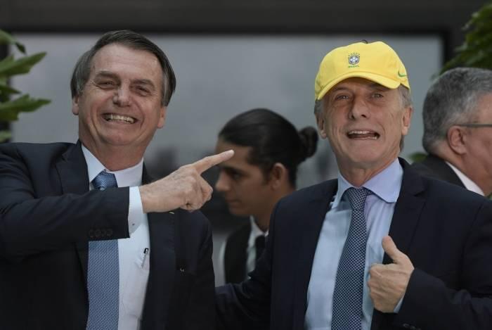 O presidente brasileiro, Jair Bolsonaro, com Mauricio Macri, vestindo um boné da seleção brasileira de futebol durante um almoço oficial na Casa Rosada