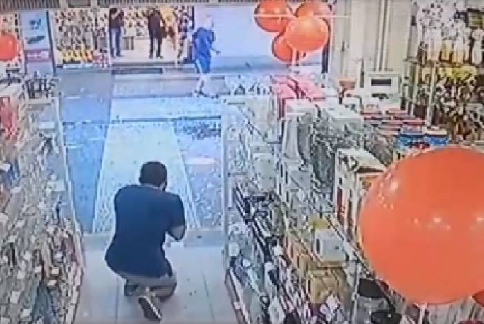 Imagem de câmera de segurança mostra momento em que ferido se ajoelha no chão com as mãos no rosto