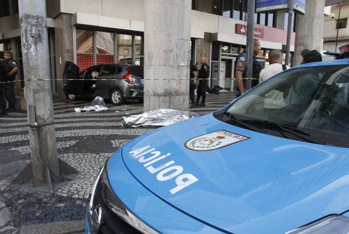 Policiais perseguiram carro de suspeitos, que terminou baleado sobre a calçada, em frente à agência bancária
