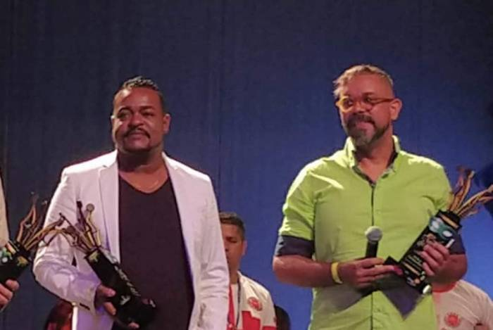 Leandro recebendo prêmio 'Plumas e Paetês 2018' como melhor aderecista junto com o carnavalesco Edson Pereira. Reconhecimento pelo trabalho na Viradouro, que disputou a Série A