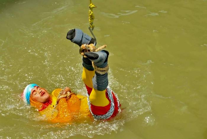 Ilusionista indiano Chanchal Lahiri, conhecido por seu nome artístico 'Jadugar Mandrake', é lançado no rio Ganges, amarrado com correntes de aço e cordas, em Kolkata
