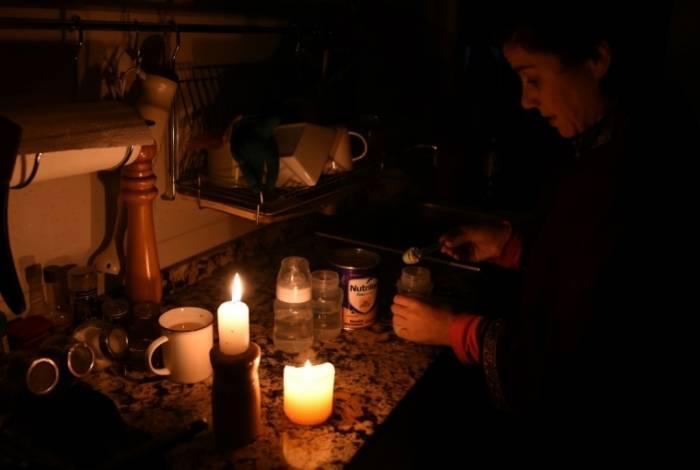 Mulher prepara mamadeira à luz de velas