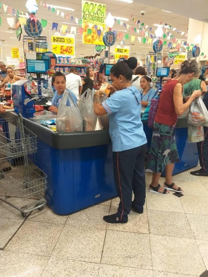 Funcionária de um supermercado guarda as compras em sacolas plásticas