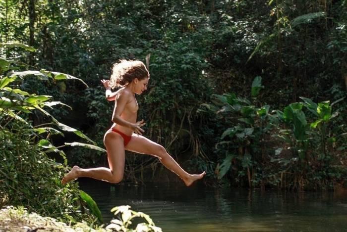 Sem a parte de cima do biquíni, Bruna Linzmeyer pula em cachoeira
