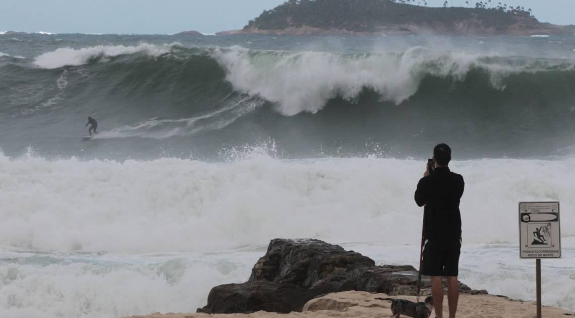 Cariocas e turistas aproveitam o fim de semana na praia mesmo com muito frio e chuva. Na foto, surfista no Leblon.