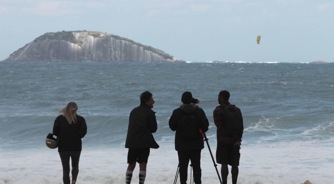 Cariocas e turistas aproveitam o fim de semana na praia mesmo com muito frio e chuva. Na foto,pessoas observam e fotografam surfistas no Leblon.