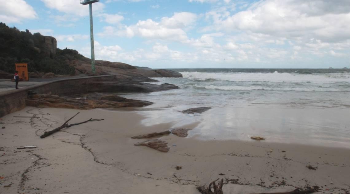 Cariocas e turistas aproveitam o fim de semana na praia mesmo com muito frio e chuva. Na foto, ressaca leva detritos e muita areia para o Arpoador.